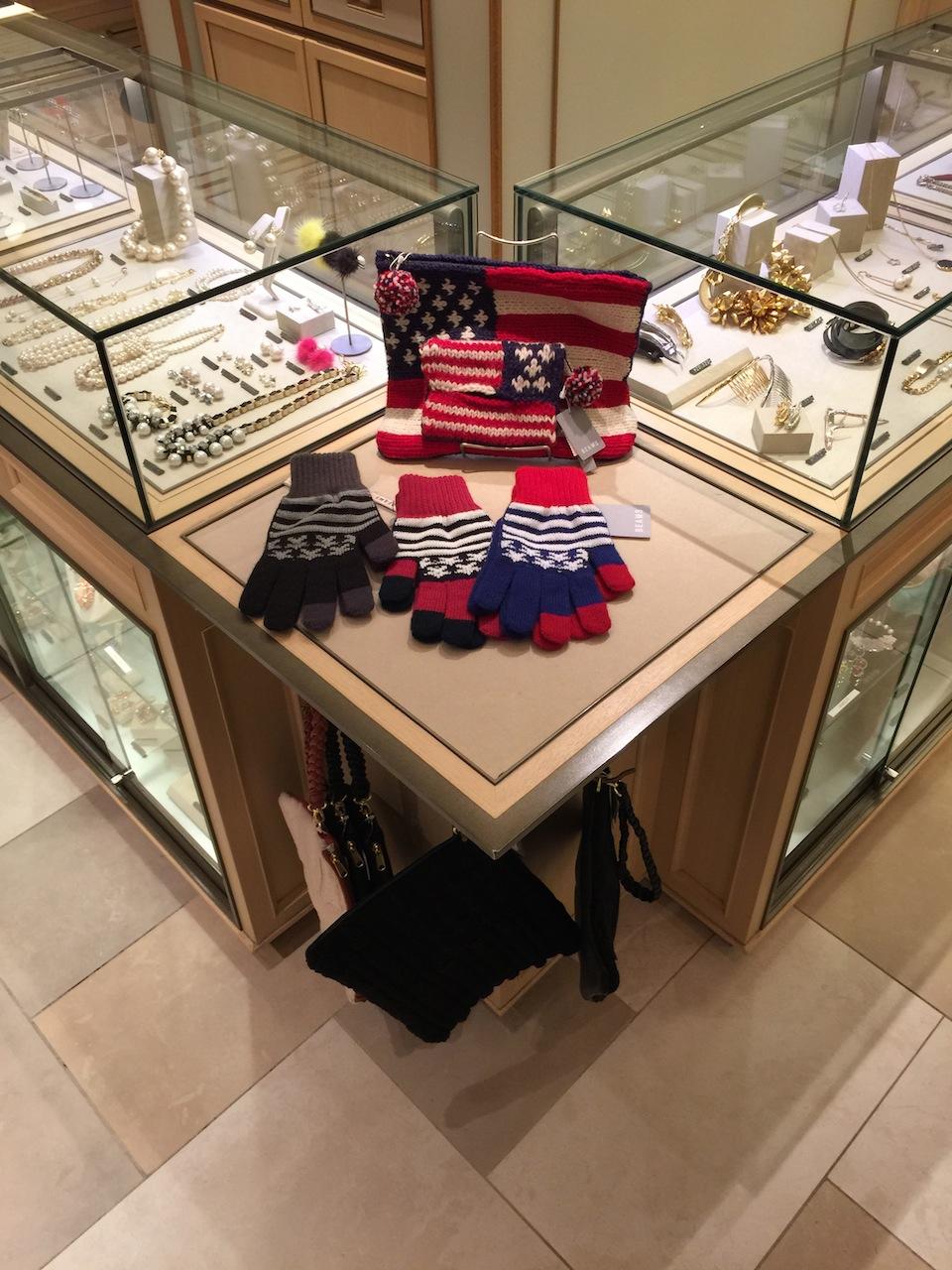 アクセサリーのケースの脇に、毛糸で編んだ手袋とポーチ