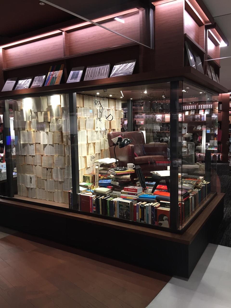 古い本が積み上げられている。壁面にも開いた洋書が貼り付けられて・・・