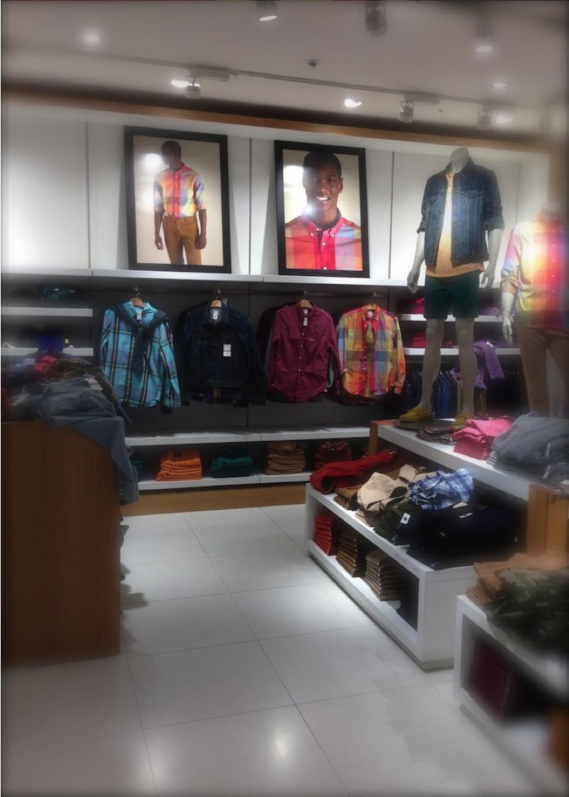 ポスターでモデルがスタイリングの着こなしを表現。その商品は直ぐ下の棚とラックで展開されている。